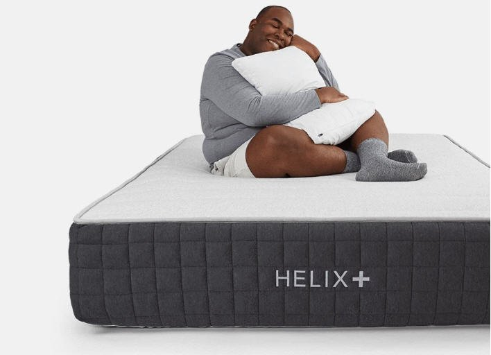Helix Plus Mattress with a heavy man on it holding a pillow while smiling