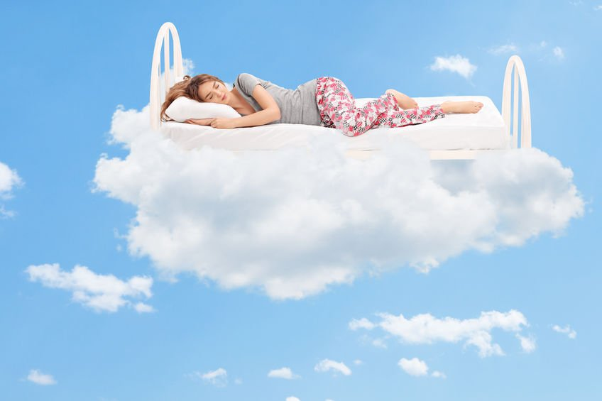 Woman sleeping on a very comfortable mattress in the clouds