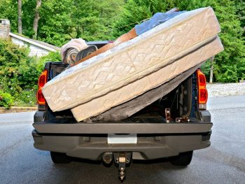A donated bed mattress being collected by a truck
